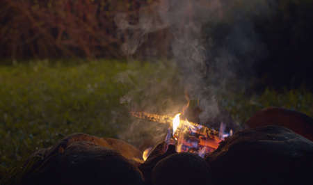 Close up bonfire in the forest at night. Burning woods and stones on the grass glade. Concept of traveling and healthy lifestyle