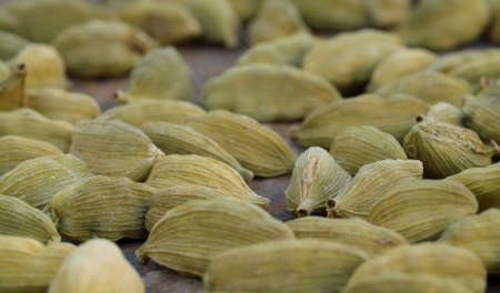 Macro shot of green dried cardamom seeds - famous aromatic spice. Extreme close up