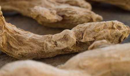 Macro shot of dried ginger roots - famous aromatic spice. Extreme close up