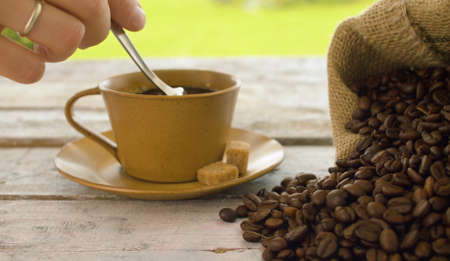 Close-up of coffee beans in a burlap jute sack and cup of coffee on a wooden table outdoors. Hand stirring sugar in a cup 写真素材