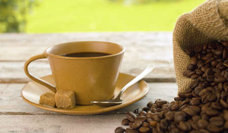 Close-up of coffee beans in a burlap jute sack and cup of coffee on a wooden table outdoors. Dolly shot