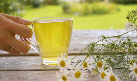 Close-up transparent cup of chamomile tea on the wooden table outdoors. A bouquet of daisies on the table. Herbal medicine concept