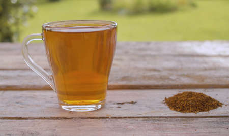 Close-up a transparent mug of rooibos tea and rooibos on the old wooden table outdoors. Healthy eating concept