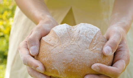 Close up homemade bread in female hands in the garden at summer. Natural organic handmade food