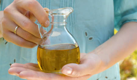 Close up olive oil in female hands in a glass jug in the garden at summer day. Healthy lifestyle concept 写真素材