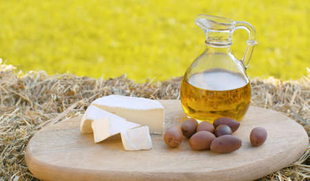 Close up olive oil in a glass jug, cheese and olives on the wooden cutting board in the garden at summer day. Healthy lifestyle concept