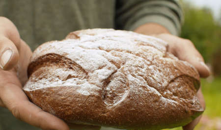 Close up homemade bread in farmers hands in the garden at summer. Natural organic handmade food 写真素材