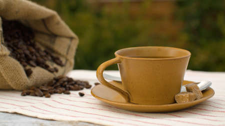 Close-up of coffee beans in a burlap jute sack and cup of coffee with raw sugar on a table in the garden 写真素材