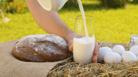 Close up milk pouring into a glass, traditional baked bread and chicken eggs on fresh hay. Natural organic handmade food