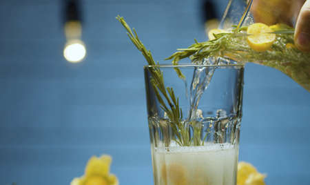 Close up pouring rosemary and physalis fizzy drink into a glass. Blurry lights on blue background