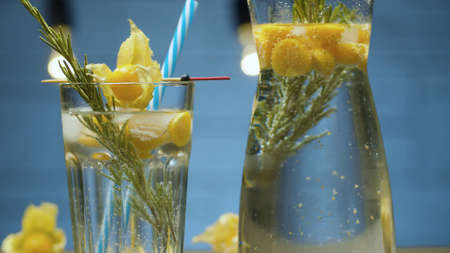Close up rosemary and physalis cold fizzy drink in a glass jug on blue background