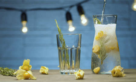 Close up sparkling water pouring into the glass jug with rosemary and physalis. Making of cold drink. Blurry lights on blue background