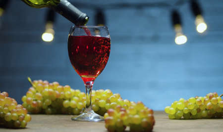 Close up red wine pouring into a glass. Bunches of grapes on the table. Blurry lamps on blue background.