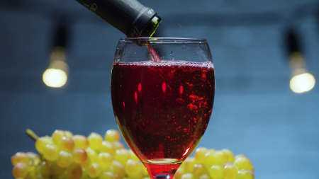 Close up red wine pouring into a glass. Bunches of grapes on the table. Blurry lamps on blue background