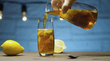 Close up male hand pouring ice tea into a glass. Blurry lamps on blue background