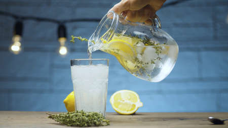 Close up pouring lemonade with thyme into a glass on blue background
