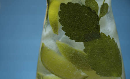 Close up lemonade with lime and mint in glass jug on blue background