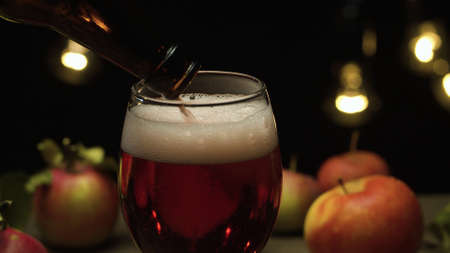 Close up delicious red apples and apple cider pouring into a glass on black background. Healthy food, vitamins, fruits