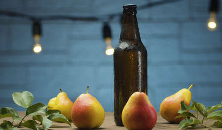 Close up male hand putting misted bottle of cider on the table on blue background. Fresh ripe pears. Healthy food, vitamins, fruits 写真素材