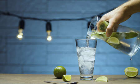 Close up male hand pouring lemonade with lime and mint into a glass. Blurry lamps on blue background