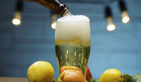 Close up delicious ripe pears and pear cider pouring into a glass on blue background. Healthy food, vitamins, fruits