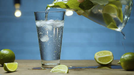 Close up pouring lemonade with lime and mint into a glass. Blurry lamps on blue background
