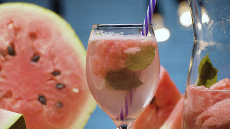 Close up watermelon lemonade in a glass. Soda water, pieces of watermelon, mint leaves and ice in glass jug. Blurry lamps on blue background