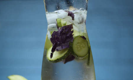 Close up vegetable fizzy drink. Sparkling water in a glass jug with sliced cucumber and purple basil leaves. Blurry bulbs on blue background 写真素材