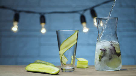 Close up cooking vegetable drink. Pouring fizzy water into a glass with sliced cucumber and purple basil leaves. Blurry bulbs on blue background