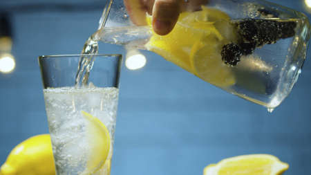 Extreme close up pouring lemonade with dewberry and lemon into a glass. Blurry lamps on blue background