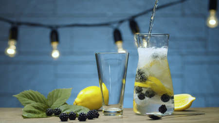 Close up cooking dewberry lemonade. Pouring soda water into a jug with dewberry, sliced lemon and ice. Blurry lamps on blue background