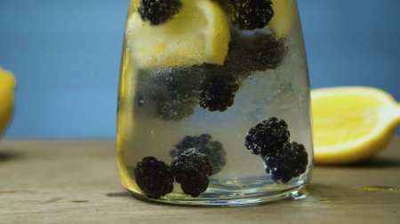 Close up dewberry lemonade in glass jug. Blurry lamps on blue background