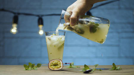 Close up male hand pouring drink with mint and passion fruit into a glass. Blurry lamps on blue background