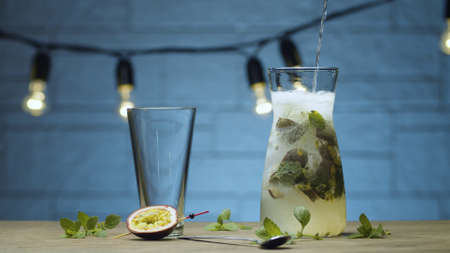 Close up pouring fizzy water in the jug with mint and passion fruit drink. Blurry lamps on blue background 写真素材