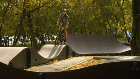 Young boy, biker riding on the pump track in the park at sunny day. Childrens sport and healthy lifestyle concept