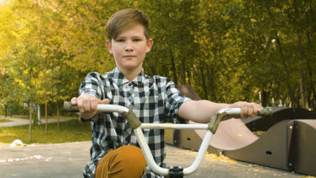 Portrait of young biker sitting on the bike in the park at sunny day. Childrens sport and healthy lifestyle concept