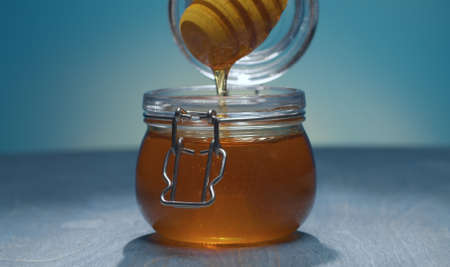 Close up honey pouring from honey spoon into a jar on blue background. Healthy fresh food concept