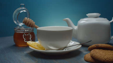 Close up white tea pot and tea cup. Honey in glass jar, lemon and cookies on the table 写真素材