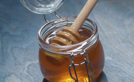 Close up fresh honey in glass jar on blue background. Healthy fresh food concept. High angle view 写真素材