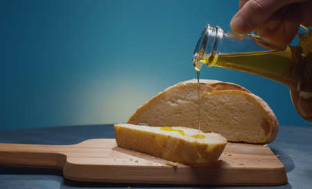 Close up male hand pouring olive oil on the piece of bread. Blue background. Healthy fresh food concept