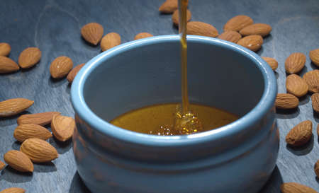 Close up fresh honey pouring into a bowl and almond nuts on blue background. Healthy fresh food concept
