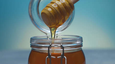 Extreme close up fresh honey pouring from honey spoon into a jar on blue background. Healthy fresh food concept. Camera flying around it. Macro