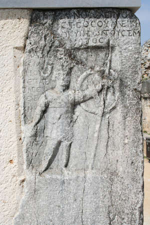 The stone engraving depicts a gladiator at the gate. This historic theater in Philippi would have been visited by the Apostle Paul, Silas, Lydia and early Christians from Acts 16. The theater would have housed dramas and gladiator fights. Stock Photo