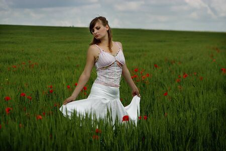 Beautiful young woman standing on the poppys field photo