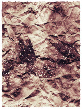 Old-fashioned abstraction from crumpled charred brown paper in a frame with watercolor spots