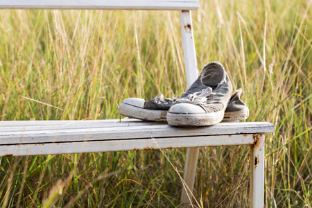 old shoes: old shoes on the white field chair with sunset and bicycle. Stock Photo