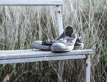 old shoes: old shoes on the white chair in the grass field  with vintage style