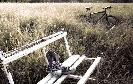 old shoes: old shoes on the white chair in the grass field with vintage style Stock Photo