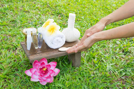 Female hand with Spa massage compress balls, herbal ball on the wooden with treaments spa, relax outdoor