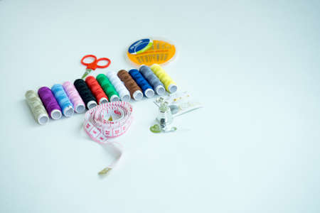 kit de costura: Sewing accessories, tools ,colorful spools, needle and measuring tapeof thread with scissors isolated on white background, top view